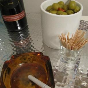 A retro ashtray and olives on a silver tray.